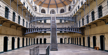 The main common area of a correctional institution, with doorways all around the room and a large metal staircase in the centre.