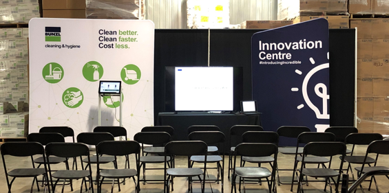 An empty conference room set up with a few Bunzl Cleaning & Hygiene pop up banners, a display and a podium.