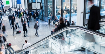 An escalator in a high traffic building looking down with many bustling people walking through hallways maintained with Bunzl Cleaning & Hygiene products.
