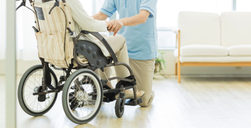 Close crop of a wheel chair from behind that shows the bottom half of someone in the chair with a long term healthcare worker kneeling down in front of them.