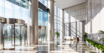 The inside of a commercial building entryway with the sun streaming through the all glass façade.