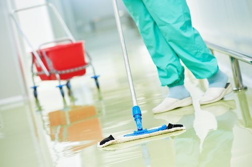 Close crop of a healthcare worker's legs and a wet mop cleaning a sparkling hallway.