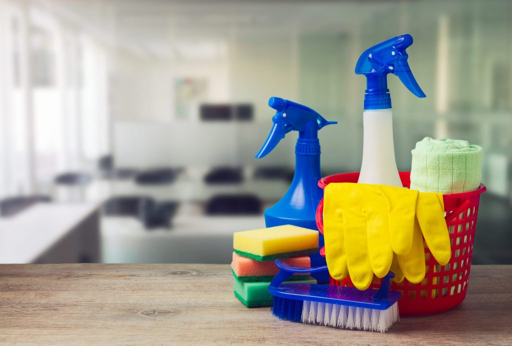 An image focused on a basket of Bunzl Cleaning & Hygiene products in an empty meeting room.