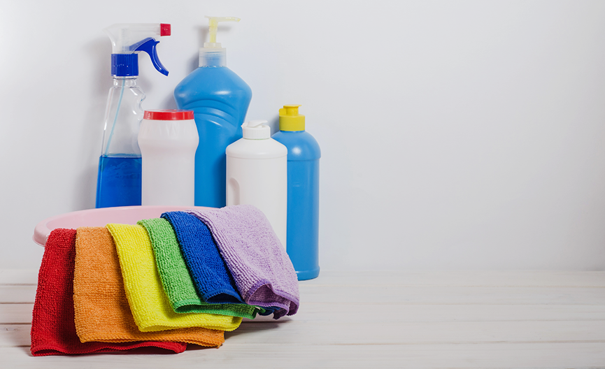 An image of cleaning solution spray and squeeze bottles sitting behind a basin with microfiber cloths in a rainbow of colours hanging on it.