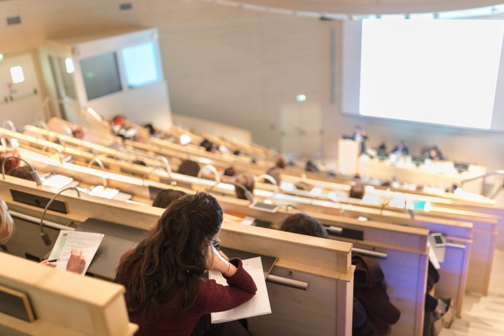 A sparkling clean lecture hall, in a facility maintained with Bunzl Cleaning & Hygiene products, with students seated listening to a lecture.