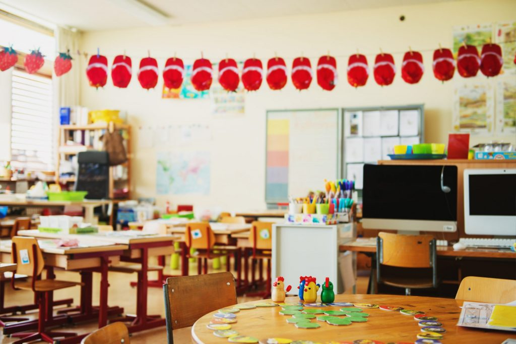 A colourful elementary school classroom with desks that have craft supplies all over them and a red apple banner on the wall.