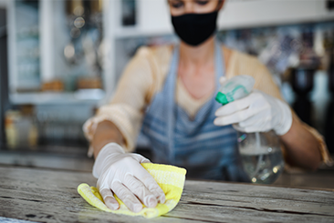 A close crop image of a young woman wearing Bunzl Cleaning & Hygiene gloves while disinfecting a table.