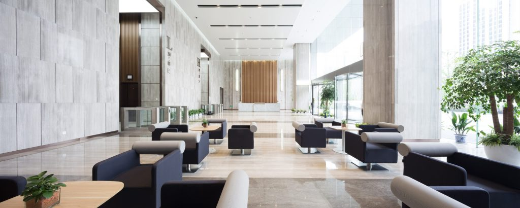 An empty and spacious commercial building lobby seating area with sparkling floors and modern navy blue furniture.