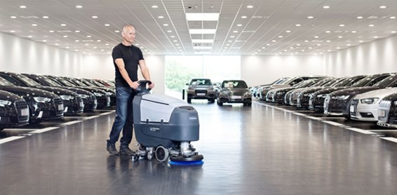 Image of man in a car showroom pushing floor scrubber equipment that has been serviced by Bunzl Cleaning & Hygiene.