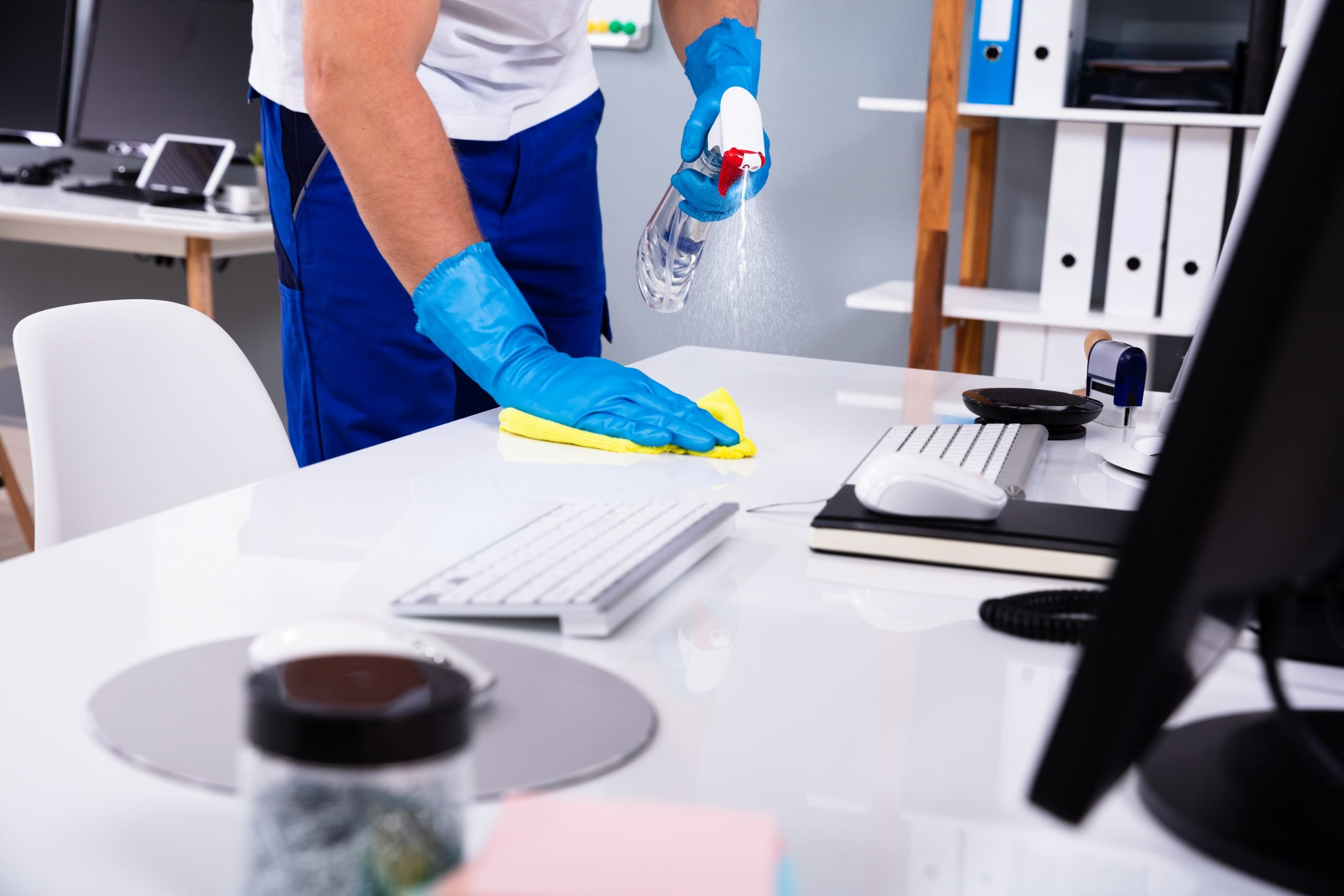 Image of cleaner wearing disposable gloves spraying an office desk.