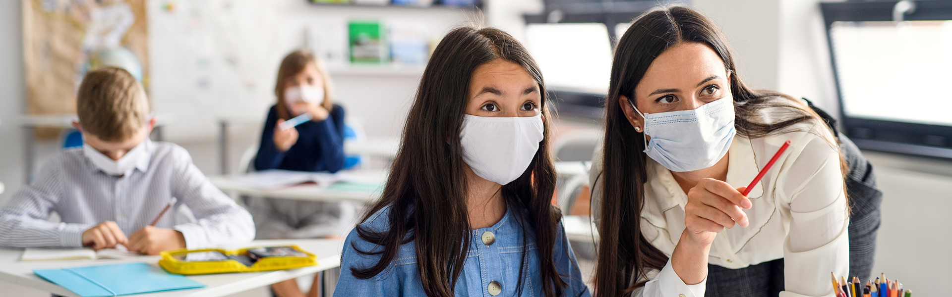 A teacher and a student wearing masks in a classroom.