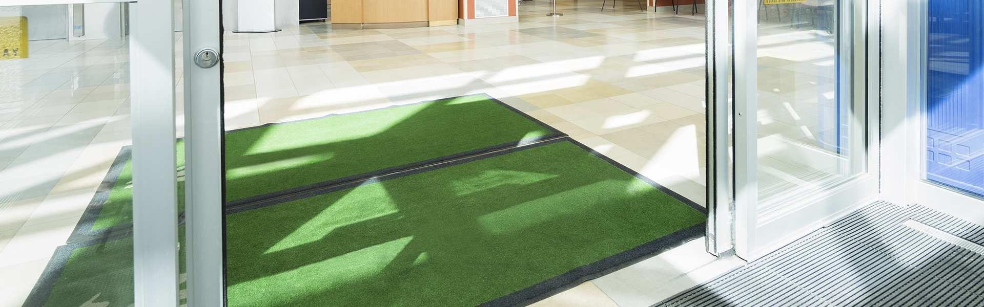 Green entrance matting in the lobby of a hospital.