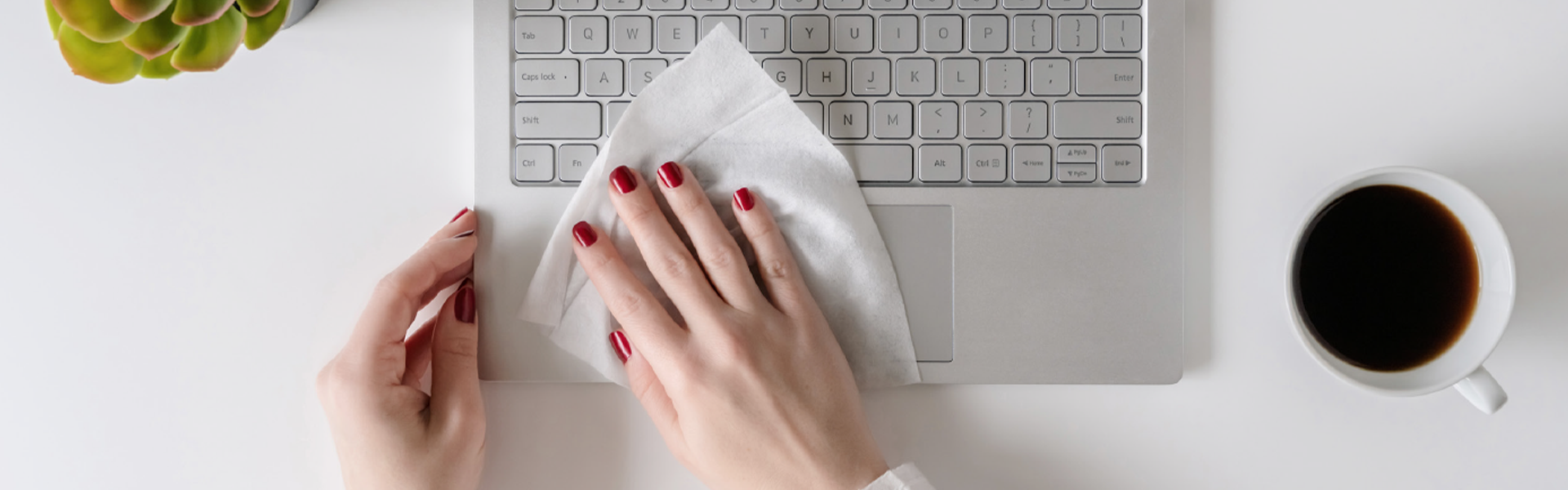 A hand with red nail polish using a sanitizing wipe to wipe down a laptop