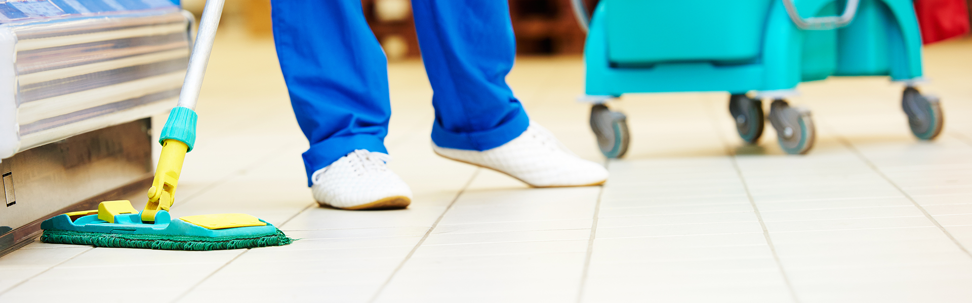 A cleaning person using a mop to clean a commercial floor.