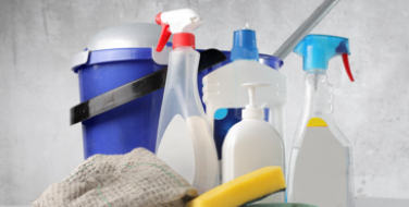 Image of building cleaning supplies including a blue bucket, mop and cleaning solution spray bottles.
