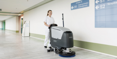 An image of a building maintenance employee using a Nilfisk Floor Care Industrial sweeper available through Bunzl Cleaning & Hygiene.